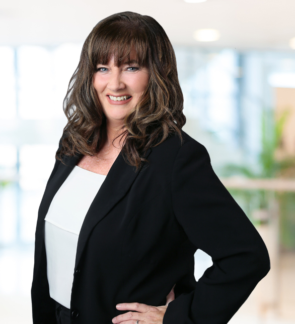 Image of Janice Quigg posing for a professional picture in a black business jacket.